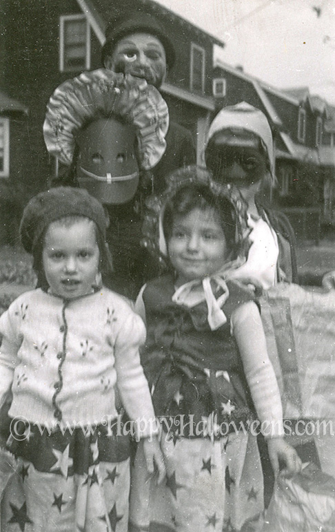 Girls in masks and bonnets and scary dudu, 1930s
