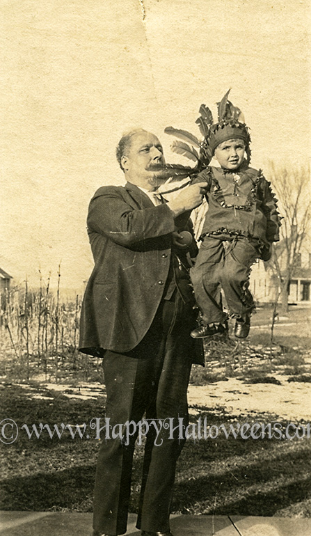 Man holds aloft a child in Native American costume - 1930s