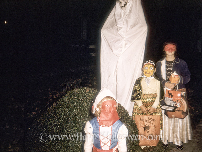 Spooky Halloween garden decoration and posed kids in masks